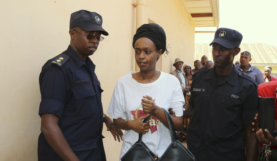 FILE - In this Friday, Oct. 6, 2017 file photo, former Rwanda presidential candidate Diane Rwigara is escorted by policemen to a court where she denied charges of insurrection and forgery that she says are linked to her criticism of the government's human rights record. As she waits for a judge to pronounce her fate on Thursday, Dec. 6, 2018, the Rwandan opposition leader accused of inciting insurrection and forgery says no amount of pressure will silence her. (AP Photo, File)