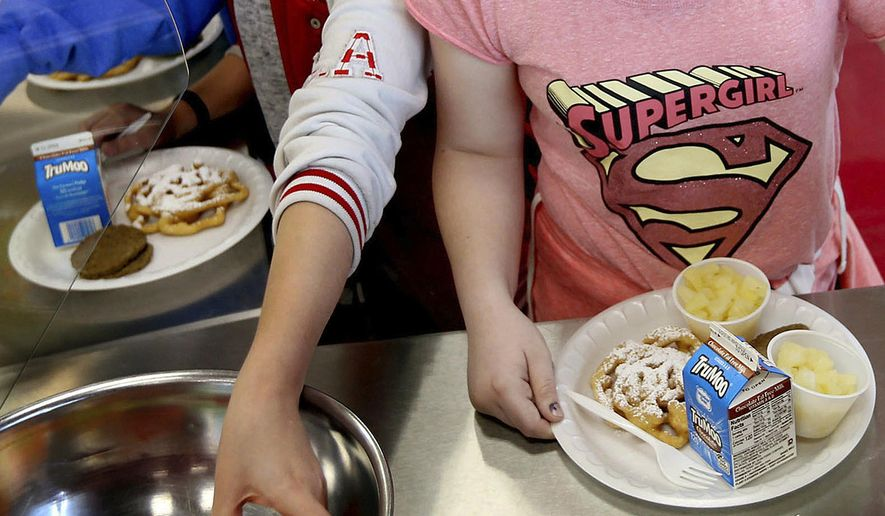 FILE - In this Friday, May 19, 2017 file photo, students line up for lunch at a middle school in Sandy, Utah. On Thursday, Dec. 6, 2018, the U.S. Department of Agriculture announced the scaling back contested school lunch standards implemented under the Obama administration, including one that required only whole grains be served. (Laura Seitz/The Deseret News via AP)