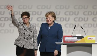 German Chancellor Angela Merkel, right, congratulates newly elected party chairwoman Annegret Kramp-Karrenbauer after the election at the party convention of the Christian Democratic Democratic Union CDU in Hamburg, northern Germany, Friday, Dec. 7, 2018. (Christian Charisius/dpa via AP)
