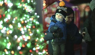 20-month-old Christopher Yuhas is mesmerized by the lights on the Christmas tree in Central Park in Johnstown, PA., while visiting with his grandmother Roseanne Menjvar, Friday, Dec.7, 2018. (John Rucosky/The Tribune-Democrat via AP)