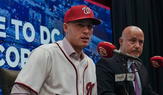 Washington Nationals President of Baseball Operations and General Manager Mike Rizzo, right, watches as new starting pitcher Patrick Corbin, left, speaks during a news conference at Nationals Park in Washington, Friday, Dec. 7, 2018. Corbin agreed to terms on a six-year contract and joins the Nationals after playing for the Arizona Diamondbacks in 2018. (AP Photo/Pablo Martinez Monsivais)