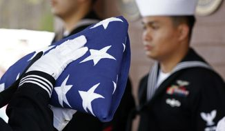 In this file photo, a Navy honor guard, from Naval Air Station Meridian, stand at attention while the American flag is prepared for presentation to the relatives of Navy Petty Officer Durell Wade, of Calhoun County, during an interment service, Friday, Dec. 7, 2018, at the North Mississippi Veterans Memorial Cemetery in Kilmichael, Miss. Wade was killed aboard the USS Oklahoma, during the Dec. 7, 1941 attack on Pearl Harbor. Determining advances in forensic science and genealogical help from families like Wade's, has allowed for a number of remains to be newly identified. (AP Photo/Rogelio V. Solis) **FILE**