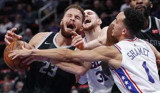 Detroit Pistons forward Blake Griffin (23) is fouled by Philadelphia 76ers forward Mike Muscala (31) as Landry Shamet (1) defends in the first half of an NBA basketball game in Detroit, Friday, Dec. 7, 2018. (AP Photo/Paul Sancya)