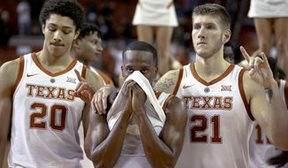 """Texas guard Matt Coleman III (2) covers his face while standing for the playing of """"The Eyes of Texas,"""" following Texas' 54-53 loss to Virginia Commonwealth in an NCAA college basketball game in Austin, Texas, on Wednesday, Dec. 5, 2018. (Nick Wagner/Austin American-Statesman via AP)"""