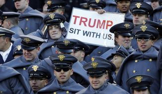 FILE - In this Saturday, Dec. 8, 2018, file photo, an Army cadet displays a sign for then President-elect Donald Trump in the first half of the Army-Navy NCAA college football game in Baltimore. President Trump will attend the Army-Navy football game, Saturday, Dec. 8, 2018, in Philadelphia. (AP Photo/Patrick Semansky, File)