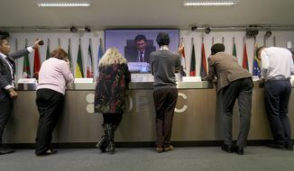 Journalists listen to a video during a meeting of the Organization of the Petroleum Exporting Countries, OPEC, and non OPEC members, at their headquarters in Vienna, Austria, Friday, Dec. 7, 2018. (AP Photo/Ronald Zak)