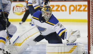 St. Louis Blues goaltender Jake Allen gloves the puck on a shot from Winnipeg Jets' Adam Lowry during the second period of an NHL hockey game Friday, Dec. 7, 2018, in Winnipeg, Manitoba. (John Woods/The Canadian Press via AP)