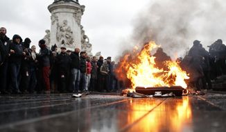 A bin is burning as school children demonstrate in Paris, Friday Dec.7, 2018. Footage showing the brutal arrest of high school students protesting outside Paris is causing a stir ahead of further anti-government protests this weekend. (AP Photo/Thibault Camus)