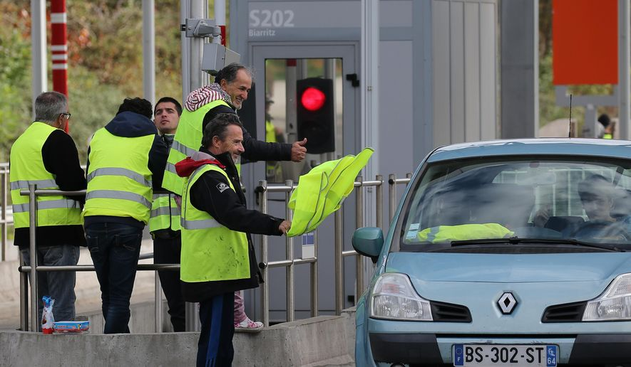 A demonstrator holds a yellow jacket as he protests at the toll gates on motorway at Biarritz southwestern France, Thursday, Dec.6, 2018. Paris police and store owners are bracing for new violence at protests Saturday, despite President Emmanuel Macron's surrender over a fuel tax hike that unleashed weeks of unrest. (AP Photo/Bob Edme)