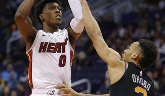 Miami Heat guard Josh Richardson (0) shoots over Phoenix Suns guard Elie Okobo during the first half of an NBA basketball game Friday, Dec. 7, 2018, in Phoenix. (AP Photo/Rick Scuteri)