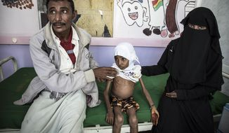 In this Nov. 15, 2018 photo, 10-year-old Affaf, who weighs 9,6 kg (21 pounds), sits with her parents at a hospital in Hajjah, Yemen. The U.N. food agency said Thursday, Dec. 6, 2018 it is planning to rapidly scale up food distribution to help another 4 million people in Yemen over the next two months, more than a 50-percent increase in the number reached now, if access can be maintained in the poor, war-stricken country. (Marco Frattini/WFP via AP)