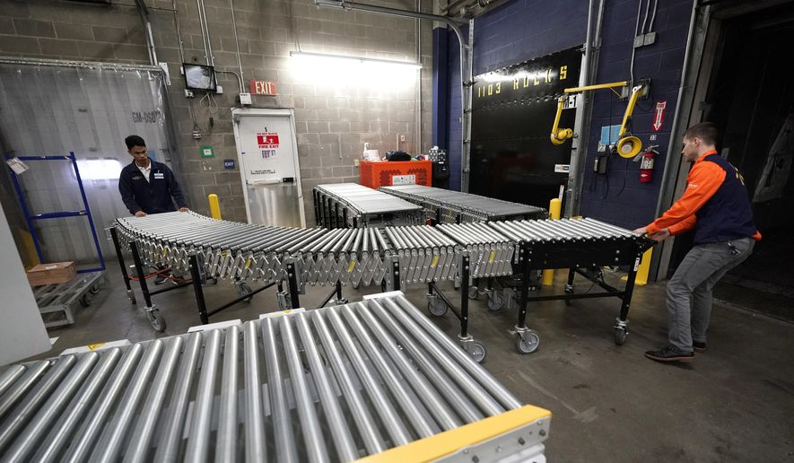 In this Nov. 9, 2018, file photo Laurence Marzo, left, and Ty Ford, right, move a conveyor belt into place to help unload a truck carrying merchandise at a Walmart Supercenter in Houston. On Friday, Dec. 7, the U.S. government issued the November jobs report. (AP Photo/David J. Phillip, File)