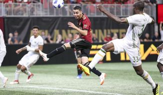 File - In this June 24, 2018, file photo, Atlanta United midfielder Miguel Almiron (10) has a shot defended by Portland Timbers defender Larrys Mabiala (33) in the second half of an MLS soccer match in Atlanta. Before an expected crowd of more than 70,000, Atlanta United will host the Portland Timbers in the MLS Cup championship game Saturday, Dec. 8, 2018. (AP Photo/Brett Davis, File)