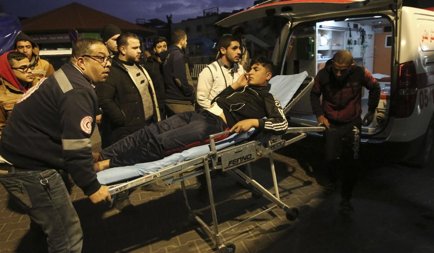 Palestinian medics move a wounded youth who was shot by Israeli troops during a protest at the Gaza Strip's border with Israel, at the Shifa hospital in Gaza City, Friday, Dec. 7, 2018. (AP Photo/Adel Hana)