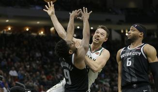 Milwaukee Bucks' Matthew Dellavedova, middle, is, fouled between Detroit Pistons' Langston Galloway (9) and Bruce Brown (6) during the second half of an NBA basketball game Wednesday, Dec. 5, 2018, in Milwaukee. (AP Photo/Aaron Gash)
