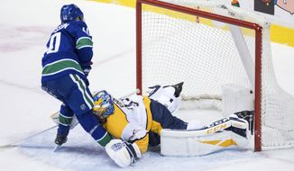 Vancouver Canucks' Elias Pettersson, left, of Sweden, scores on a penalty shot against Nashville Predators goalie Pekka Rinne, of Finland, during the second period of an NHL hockey game Thursday, Dec. 6, 2018, in Vancouver, British Columbia. (Darry Dyck/The Canadian Press via AP)