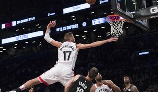 Brooklyn Nets forward Joe Harris (12) fouls Toronto Raptors center Jonas Valanciunas (17) during the first half of an NBA basketball game, Friday, Dec. 7, 2018, in New York. (AP Photo/Mary Altaffer)