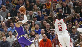 Utah Jazz guard Ricky Rubio (3) shoots as Houston Rockets center Clint Capela (15) defends during the first half during an NBA basketball game Thursday Dec. 6, 2018, in Salt Lake City. (AP Photo/Rick Bowmer)