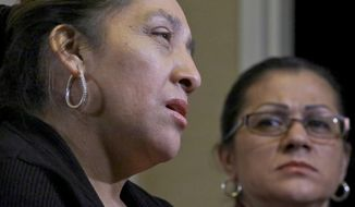 Sandra Diaz, right, listens as Victorina Morales, right, recalls her experience working at President Donald Trump's golf resort in Bedminster, N.J., during an interview, Friday Dec. 7, 2018, in New York. Both Morales and Diaz say they used false legal documents to get hired at the resort and supervisors knew it. (AP Photo/Bebeto Matthews)