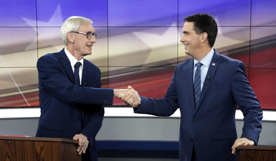 In this Oct. 19, 2018, file photo, Democratic challenger Tony Evers, left, and Wisconsin Gov. Scott Walker, a Republican, shake hands during a gubernatorial debate in Madison, Wis. (Steve Apps/Wisconsin State Journal via AP, File)
