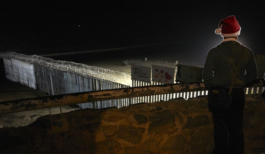 "Javier Hernanez, of Tijuana, Mexico, wears a Christmas hat as he looks out over the razor-wire topped border wall separating Tijuana from San Diego Friday, Dec. 7, 2018, in Tijuana, Mexico. President Donald Trump said Friday that Congress should provide all the money he wants for his promised U.S.-Mexico border wall, and he called illegal immigration a ""threat to the well-being of every American community."" (AP Photo/Gregory Bull)"
