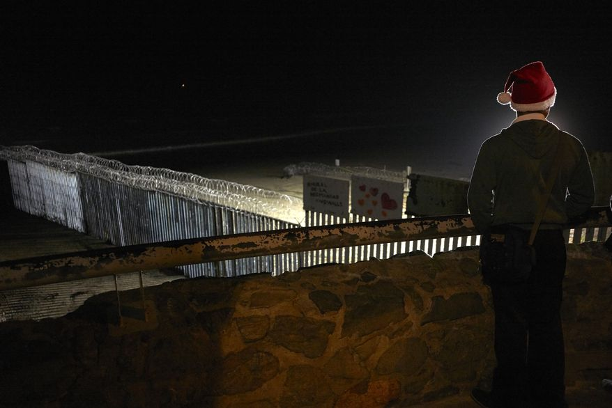 """Javier Hernanez, of Tijuana, Mexico, wears a Christmas hat as he looks out over the razor-wire topped border wall separating Tijuana from San Diego Friday, Dec. 7, 2018, in Tijuana, Mexico. President Donald Trump said Friday that Congress should provide all the money he wants for his promised U.S.-Mexico border wall, and he called illegal immigration a """"threat to the well-being of every American community."""" (AP Photo/Gregory Bull)"""