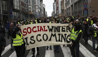 Protestors hold a banner which reads 'social winter is coming' during a demonstration in Brussels, Saturday, Dec. 8, 2018. Hundreds of police officers are being mobilized in Brussels Saturday, where yellow vest protesters last week clashed with police and torched two police vehicles. More than 70 people were detained. (AP Photo/Francisco Seco)