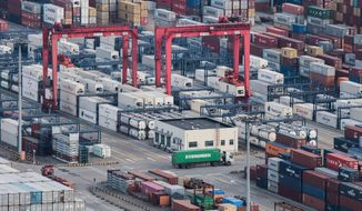 FILE - In this March 29, 2018, file photo, a cargo truck drives amid stacked shipping containers at the Yangshan port in Shanghai. China's export growth sank in November, 2018, as global demand weakened, adding to pressure on Beijing ahead of trade talks with Washington. (AP Photo/File)