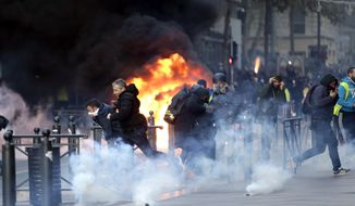 People run away from a burning car during clashes, Saturday, Dec. 8, 2018 in Marseille, southern France. The grassroots movement began as resistance against a rise in taxes for diesel and gasoline, but quickly expanded to encompass frustration at stagnant incomes and the growing cost of living. (AP Photo/Claude Paris)
