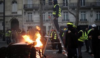 A demonstrator stands on a stepladder during clashes Saturday, Dec. 8, 2018 in Paris. Crowds of yellow-vested protesters angry at President Emmanuel Macron and France's high taxes tried to converge on the presidential palace Saturday, some scuffling with police firing tear gas, amid exceptional security measures aimed at preventing a repeat of last week's rioting. (AP Photo/Rafael Yaghobzadeh)