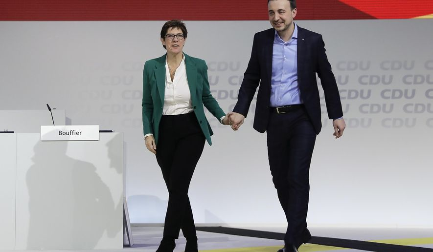 CDU party chairwoman Annegret Kramp-Karrenbauer, left, congratulates the newly elected party's general secretary Paul Ziemiak, right, during a party convention of the Christian Democratic Party CDU in Hamburg, Germany, Saturday, Dec. 8, 2018. (AP Photo/Markus Schreiber)