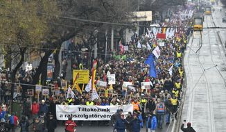 Participants march on the Szent Istvan Boulevard during the demonstration of the Hungarian Trade Union Confederation in Budapest, Hungary, Saturday, Dec. 8, 2018. The protest was held against planned 50 days overwork in a year and for freedom of scientific research and the freedom of education. (Zsolt Szigetvary/MTI via AP)