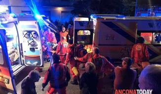 Rescuers assist injured people outside a nightclub in Corinaldo, central Italy, early Saturday, Dec. 8, 2018. At least six people, all but one of them minors, were killed and about 35 others injured in a stampede of panicked concertgoers early Saturday at a disco in a small town on Italy's central Adriatic coast. (Stefano Pagliarini/Ancona Today via AP)