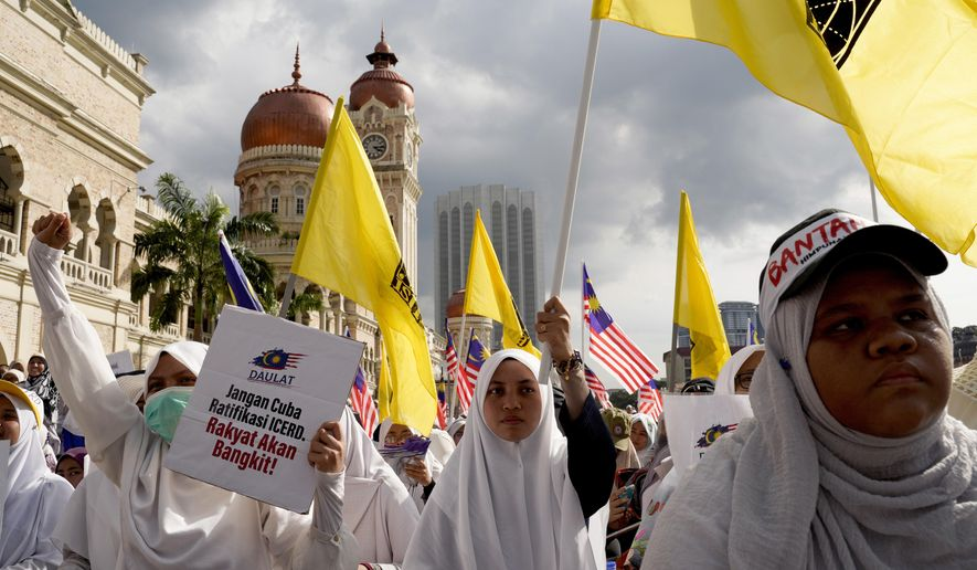Thousands of protesters take a part in a rally to celebrate the government's move to withdraw plans to ratify a U.N. anti-discrimination convention at Independent Square in Kuala Lumpur, Malaysia, Saturday, Dec. 8, 2018. Thousands of Malaysian Muslims are rallying in Kuala Lumpur against any attempt to strip ethnic Malay majority of their privileges, in the first massive street gathering since Prime Minister Mahathir Mohamad's alliance won a historic vote in May.(AP Photo/Yam G-Jun)