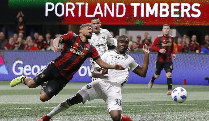 Atlanta United forward Josef Martinez (7) and Portland Timbers defender Larrys Mabiala (33) fight for the ball during the first half of the MLS Cup championship soccer game, Saturday, Dec. 8, 2018, in Atlanta. (AP Photo/Todd Kirkland)