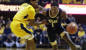 Pittsburgh guard Xavier Johnson (1) drives past West Virginia guard James Bolden (3) during the first half of an NCAA college basketball game Saturday, Dec. 8, 2018, in Morgantown, W.Va. (AP Photo/Raymond Thompson)