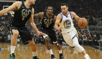 Golden State Warriors' Stephen Curry drives past Milwaukee Bucks' Eric Bledsoe and Brook Lopez during the first half of an NBA basketball game Friday, Dec. 7, 2018, in Milwaukee. (AP Photo/Morry Gash)