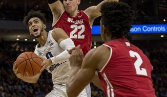 Marquette guard Markus Howard, left, is defended by Wisconsin during the first half of an NCAA college basketball game Saturday, Dec. 8, 2018, in Milwaukee. (AP Photo/Darren Hauck)