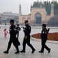 In this Nov. 4, 2017 photo, Uighur security personnel patrol near the Id Kah Mosque in Kashgar in western China's Xinjiang region. Authorities are using detentions in political indoctrination centers and data-driven surveillance to impose a digital police state in the region of Xinjiang and its Uighurs, a 10-million strong, Turkic-speaking Muslim minority Beijing fears could be influenced by extremism. (AP Photo/Ng Han Guan)