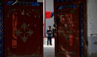 As a Uighur child played alone, China's Communist Party was showcasing Hotan Unity New Village, part of its efforts to tame Xinjiang province, the heartland of the country's often restive Uighur Muslim minority. (Associated Press/File)
