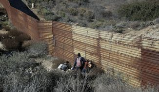 Migrant family members move into a hole to cross under the U.S. border wall, aided by two local guides, in Tijuana, Mexico, Sunday, Dec. 9, 2018. Discouraged by the long wait to apply for asylum through official ports of entry, many Central American migrants from recent caravans are choosing to cross the U.S. border wall illegally and hand themselves in to Border Patrol agents to request asylum. (AP Photo/Rebecca Blackwell)