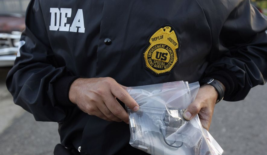 A DEA agent shows a gun allegedly seized from a suspected drug dealer after his arrest during a raid on a public housing project in Mayaguez, Puerto Rico, Friday, July 9, 2010. Hundreds of U.S. drug agents and Puerto Rican police swept through public housing projects on the island's west coast in an attempt to dismantle drug trafficking gangs and reduce crime in Mayaguez, the host city of the XXI Central American and Caribbean Games that will be inaugurated on July 17. (AP Photo/Andres Leighton)