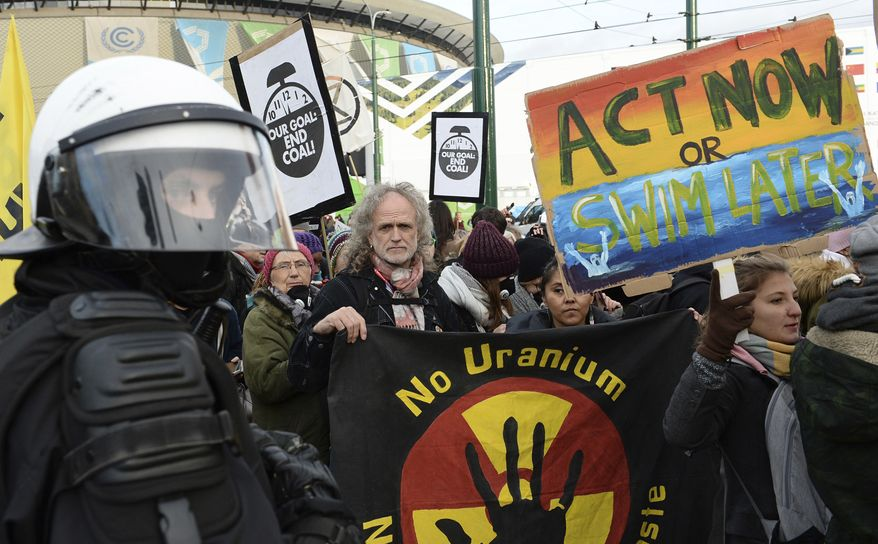 Climate activists stop in front of the COP24 UN Climate Change Conference venue during the March for Climate in a protest against global warming in Katowice, Poland, Saturday, Dec. 8, 2018. (AP Photo/Alik Keplicz)