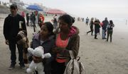 A Honduran migrant and her daughter stand on the beach looking toward the U.S. border wall, moments before suddenly squeezing through a gap and pushing through fencing to emerge on U.S. soil, in Tijuana, Mexico, Sunday, Dec. 9, 2018. Discouraged by the long wait to apply for asylum through official ports of entry, many Central American migrants from recent caravans are choosing to cross the U.S. border wall illegally and hand themselves in to Border Patrol agents to request asylum. (AP Photo/Rebecca Blackwell)