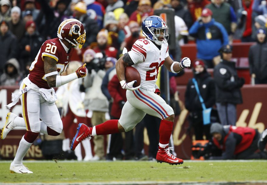 New York Giants running back Saquon Barkley (26) runs away from Washington Redskins strong safety Ha Ha Clinton-Dix (20) for a 78-yard touchdown during the first half of an NFL football game Sunday, Dec. 9, 2018, in Landover, Md. (AP Photo/Patrick Semansky) **FILE**