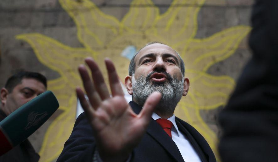 Acting Armenian Prime Minister Nikol Pashinian gestures as he leaves a polling station during an early parliamentary election in Yerevan, Armenia, Sunday, Dec. 9, 2018. The charismatic 43-year-old Nikol Pashinian took office in May after spearheading massive protests against his predecessor's power grab that forced the politician to step down. (Vahan Stepanyan/PAN Photo via AP)
