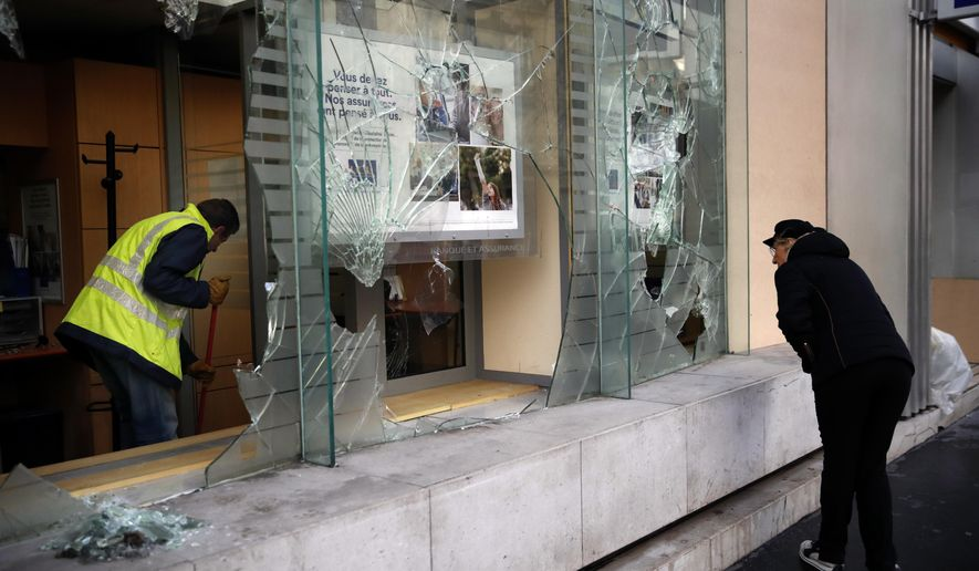 A worker clears debris in a bank as a man watches through smashed windows, in Paris, Sunday, Dec. 9, 2018. Paris monuments reopened, cleanup workers cleared debris and shop owners tried to put the city on its feet again Sunday, after running battles between yellow-vested protesters and riot police left 71 injured and caused widespread damage to the French capital. (AP Photo/Christophe Ena)