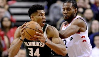 Toronto Raptors forward Kawhi Leonard (2) puts pressure on Milwaukee Bucks forward Giannis Antetokounmpo (34) as he looks for the pass during second half NBA basketball action in Toronto on Sunday, Dec. 9, 2018. (Frank Gunn/The Canadian Press via AP)