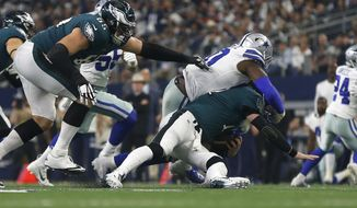 Philadelphia Eagles quarterback Carson Wentz (11) is sacked by Dallas Cowboys defensive end Demarcus Lawrence (90) during the first half of an NFL football game, in Arlington, Texas, Sunday, Dec. 9, 2018. (AP Photo/Ron Jenkins)