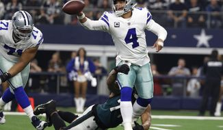 Dallas Cowboys quarterback Dak Prescott (4) is pressured by Philadelphia Eagles defensive end Michael Bennett (77) during the first half of an NFL football game, in Arlington, Texas, Sunday, Dec. 9, 2018. (AP Photo/Tony Gutierrez)